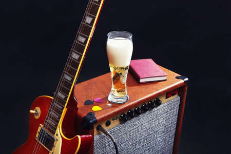 Combo amplifier for electric guitar with guitar, glass of beer and notepad on the black background.
