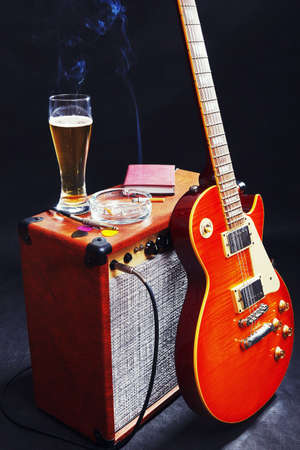 Guitar combo with guitar, glass of beer and smoking cigarette on the black background.