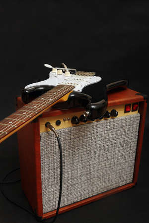Brown tube amplifier for guitar with black guitar on the black background.
