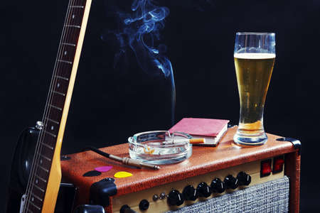 Combo for electric guitar with black guitar, glass of beer and smoking cigarette on the black background.