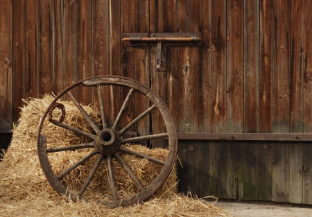 the old antique wheel from cart on background of hay and barn Stock Photo