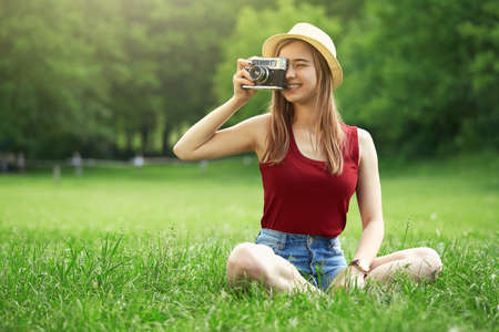 cute girl with camera on grass summer Standard-Bild