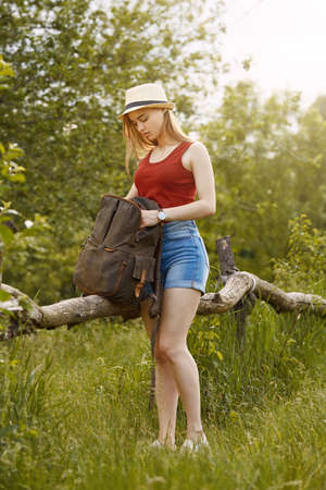 Young girl on nature with hat and backpack. Summer Standard-Bild