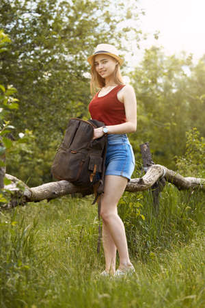 Young girl on nature with hat and backpack. Summer Stock Photo