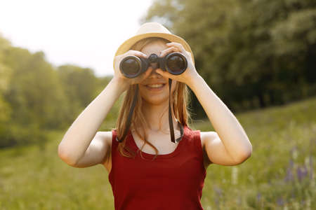 Young girl on nature with hat and binocular. Summer
