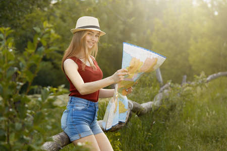 Young girl on nature with hat and map. Summer