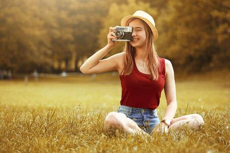 cute girl with camera on grass autumn Standard-Bild