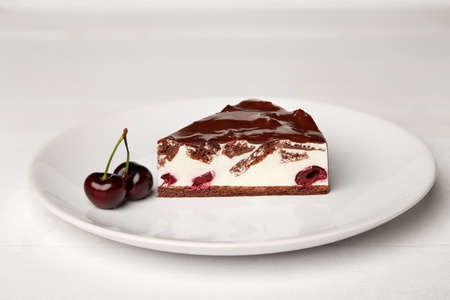 Sweat cake with cherry on plate on wooden background
