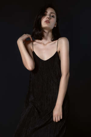 Beautiful girl in long black dress on black background possing Standard-Bild