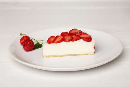 Sweat cake with strawberry on plate on wooden background