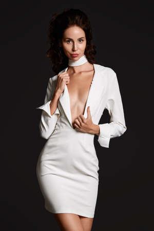 Attractive brunette slim woman in white suit at studio black background