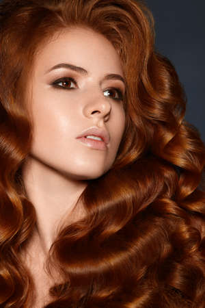 Attractive ginger woman with wave hairstyle curly in studio redhead Standard-Bild