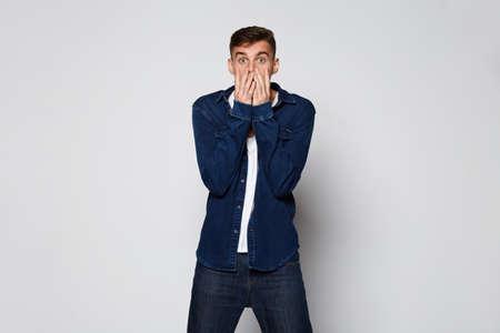 Casual emotional Man surprising on white background at studio Standard-Bild