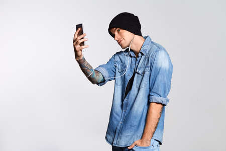 Handsome man is taking selfie and smilling on white wall at studio