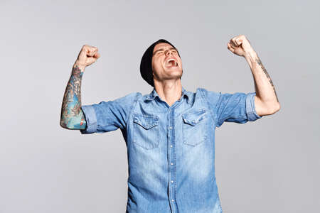 Handsome man is yelling and enjoy success on white wall at studio