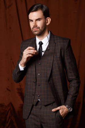 Handsome man in suit is possing and look aside on gray background at studio