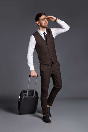 Handsome man in suit is possing and looking away and holding suitcase on gray background at studio