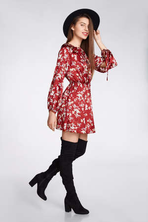 Attractive happy girl is possing and smilling in flower red dress and black hat on white at studio