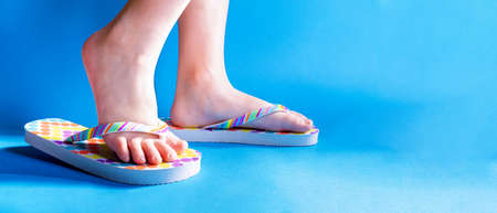 Closeup child feet wearing a pair of fun bright flip-flops on blue background. Kids and family lifestyle outdoors. The concept of children's and family vacations in the water or summer holidays.