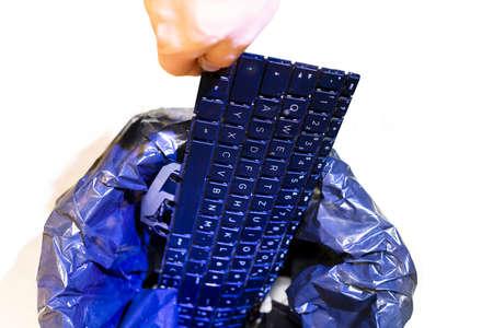 La main masculine met le clavier dans la corbeille du bureau. Poubelle isolée, vue de dessus. Concept de recyclage et de récupération des déchets électroniques et de la gestion de la réutilisation. L'ancien appareil de déchets électroniques est prêt pour le recyclage.