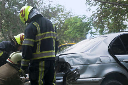 Rescue service team is working with broken car. Car crash accident. Stockfoto
