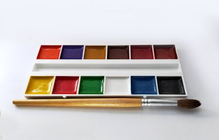 set of watercolor paints in a white container. paint and brush isolated on white background