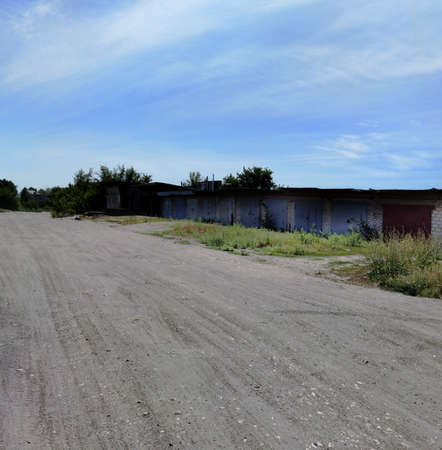 Old garages and barns near dusty road in rural countryside. Village or small town landscape. 版權商用圖片