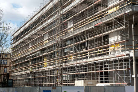 entire: Scaffolding at construction site at the entire length of building  Stock Photo