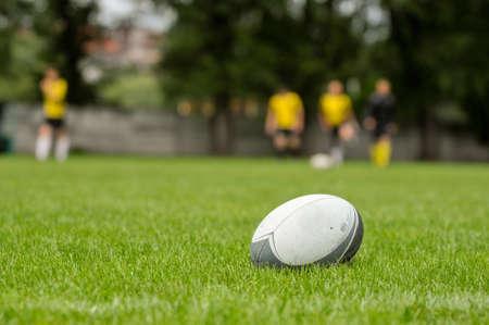 緑の草のラグビーのトレーニングで撮影した写真にラグビーのボール 写真素材