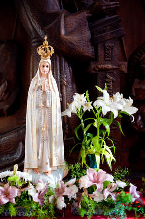 Statue of Virgin Mary from Lourdes in flowers and in golden crown