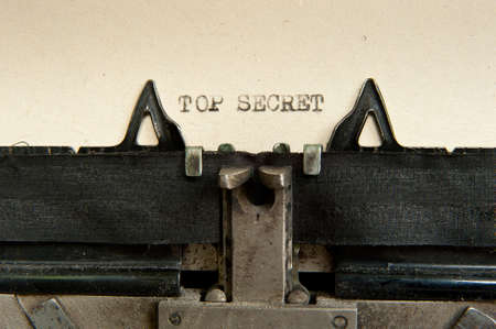 secret information: top secret phrase written with old typewriter at old, yellow sheet of paper