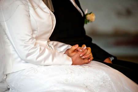 catholic wedding: Wife and housband are holding hands  Bride has a manicure  Ring on finger