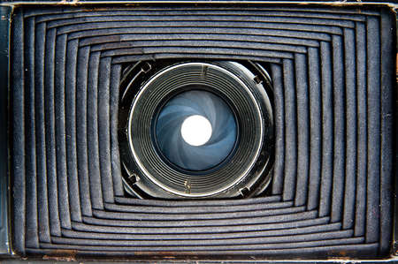 Inside vintage camera concept  View threw harmonica bellows and lens