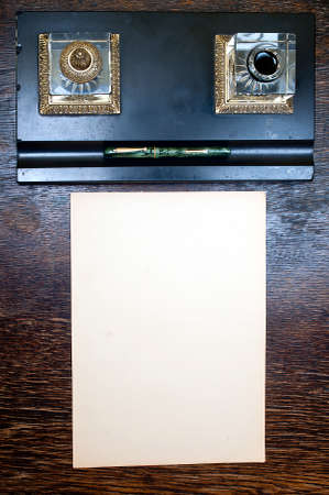 inkstand: retro inkstand, yellowed sheet of a paper at old wooden desk  Stock Photo