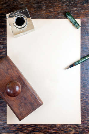 top view of old yellowed sheet of paper at wooden vintage desk  fountain pen, inkstand with black ink and blotting paper  photo