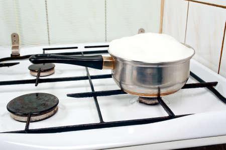 ストーブの鍋に溢れる牛乳を沸騰上
