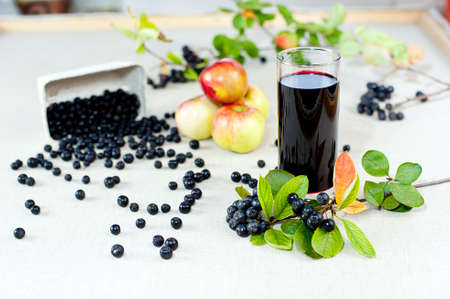 choke: Aronia - Black Choke berry fruits and juice  Separated pile of fruit, twig with leaves, and bunch