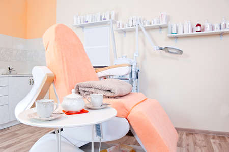 Interior of massage room  Massage chair and tea table with kettle and cups