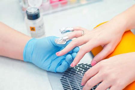 Removendo manicure h�brido de idade em um sal�o de beleza usando acetona e papel alum�nio tampas