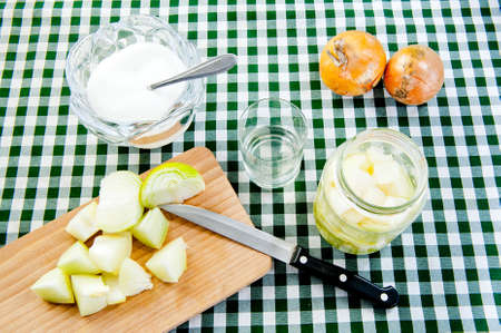 onion at wooden desk, sugar bowl onions and glass of onion syrup at table  Stock Photo