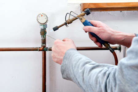 Plumber using welding gas torch to solder copper central heating pipes  photo