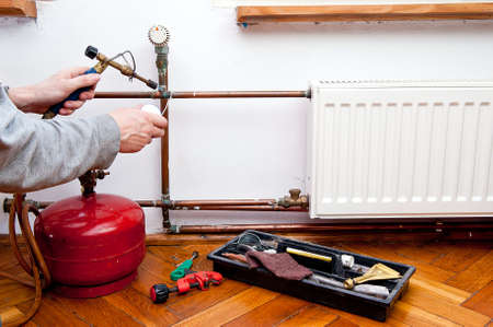 copper: Plumber using welding gas torch to solder copper central heating pipes  Stock Photo