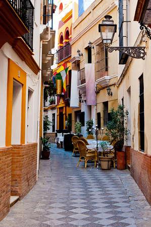 Beco estreito espanhol, com cadeiras e mesas em Sevilha