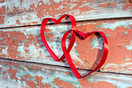 Two red heart made of ribbon against old cracked boards - side view  photo