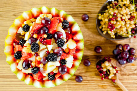 Fresh fruit summer salad in watermelon bowl at wooden background photo