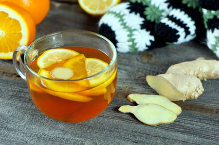 glass cup of warming ginger tea with slices of orange and lemon. Winter woolen gloves and tea container in background. photo