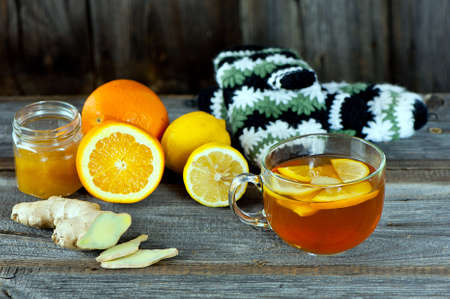 glass cup of warming ginger tea with slices of orange and lemon. Winter woolen gloves  at background. photo