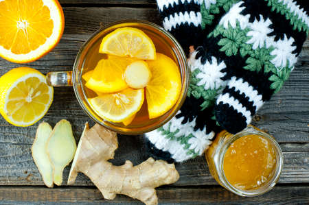 fresh ginger: glass cup of warming ginger tea with slices of orange and lemon. Winter woolen gloves and tea container in background.