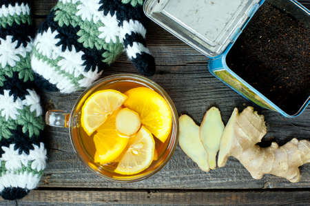 warm drink: glass cup of warming ginger tea with slices of orange and lemon. Winter woolen gloves and tea container in background.
