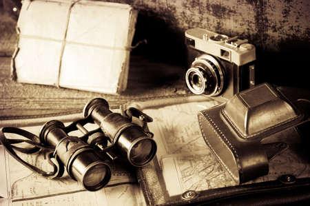 ヴィンテージ旅行思い出の概念。ビネットの地図と古いカメラ、双眼鏡、手紙、マップ ホルダー